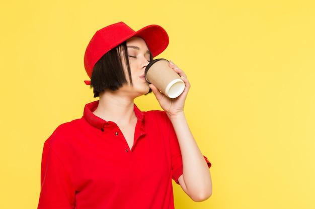 Un corriere femmina giovane vista frontale in uniforme rossa guanti neri e tappo rosso bere caffè