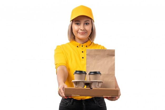 Un corriere femminile di vista frontale in cappello giallo yellwo camicia e jeans neri in possesso di coffe e pacchetto alimentare su uniforme bianca
