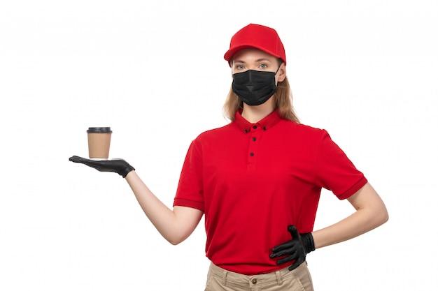 Un corriere femminile di vista frontale in guanti rossi della camicia rossa della camicia rossa maschera nera che tiene caffè su bianco