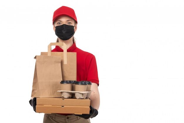 Un corriere femminile di vista frontale in guanti rossi della camicia rossa della protezione rossa e pacchetti neri e caffè dell'alimento della tenuta della maschera nera su bianco