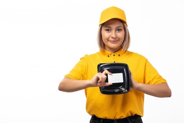 Un corriere femminile di vista frontale in jeans neri del cappuccio giallo della camicia gialla che tengono le ciotole con la carta bianca dell'alimento che sorride sul bianco