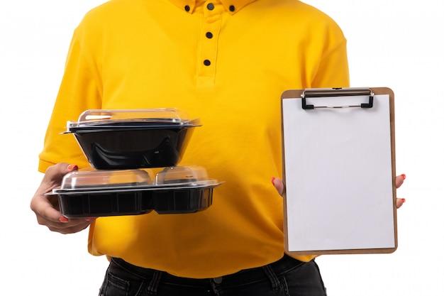 Un corriere femminile di vista frontale in jeans neri del cappuccio giallo della camicia gialla che tengono le ciotole con la carta dell'alimento su bianco