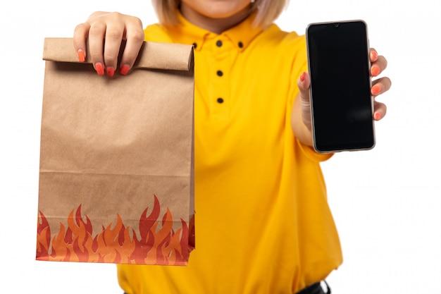 Un corriere femminile di vista frontale in smartphone giallo della tenuta del shrit e pacchetto dell'alimento sull'uniforme bianca