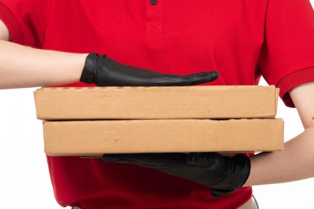 Un corriere femminile vista frontale in guanti neri camicia rossa che tengono scatole di pizza