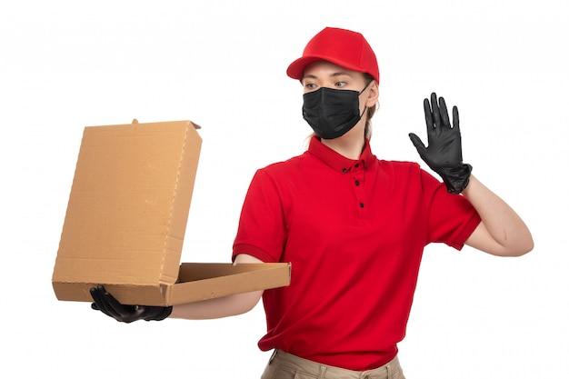 Un corriere femminile vista frontale in guanti rossi camicia rossa berretto nero e maschera nera in possesso di scatola per pizza vuota