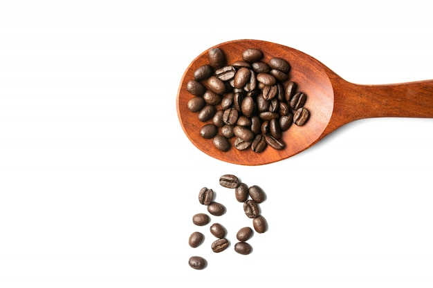 Un cucchiaio di legno con chicchi di caffè sparsi isolati su sfondo bianco e copia spazio