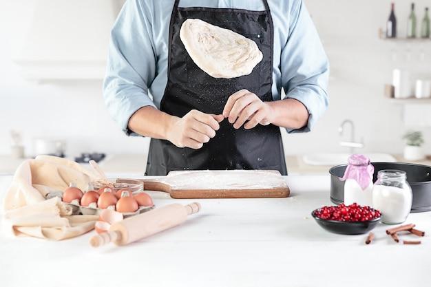 Un cuoco in una cucina rustica. il maschio passa con ingredienti per cucinare prodotti a base di farina o pasta, pane, muffin, torte, torte, pizza