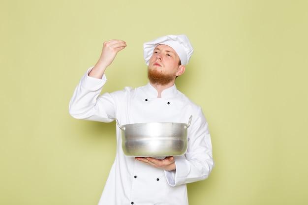 Un cuoco maschio giovane di vista frontale in cappuccio bianco bianco del cappuccio del vestito del cuoco della tenuta che tiene pentola d'argento
