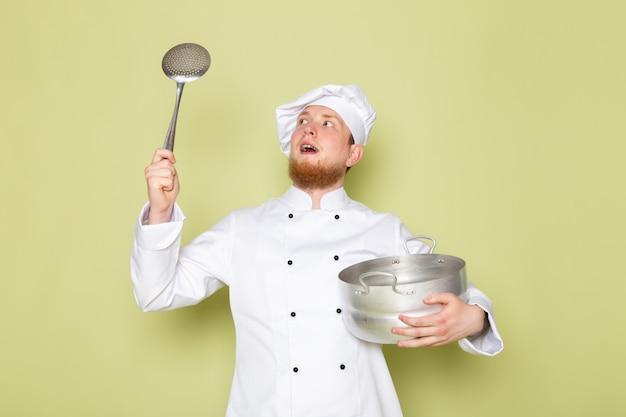 Un cuoco maschio giovane di vista frontale in cappuccio bianco bianco del vestito del cuoco del cuoco unico che tiene casseruola d'argento e grande cucchiaio d'argento
