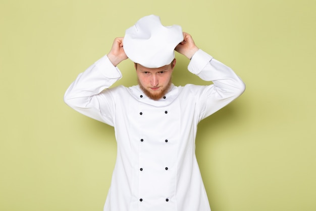 Un cuoco maschio giovane di vista frontale in vestito bianco del cuoco che porta la protezione bianca della testa