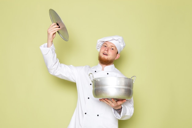 Un cuoco maschio giovane di vista frontale in vestito bianco del cuoco copricapo bianco che tiene casseruola d'argento e la sua protezione