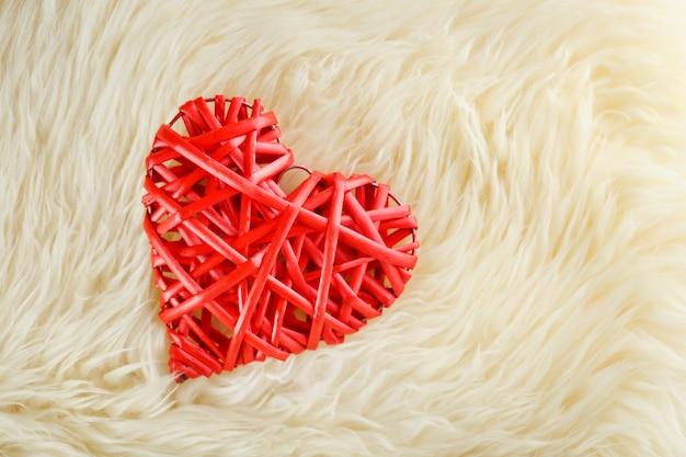 Un cuore rosso di vimini giace su di noi in una coperta di lana bianca, concetto di san valentino