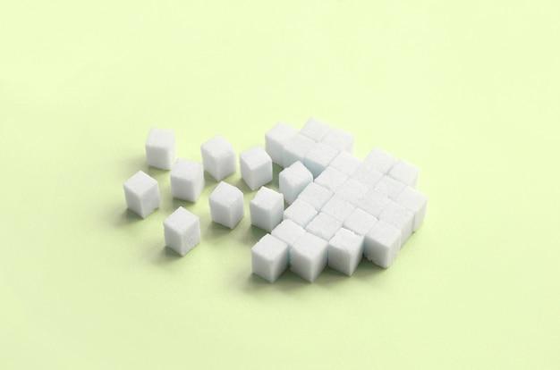 Un cuore spezzato fatto di zollette di zucchero giace su un lime pastello alla moda