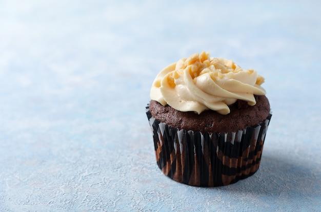 Un cupcake al cioccolato con crema al caramello e arachidi su uno sfondo blu.