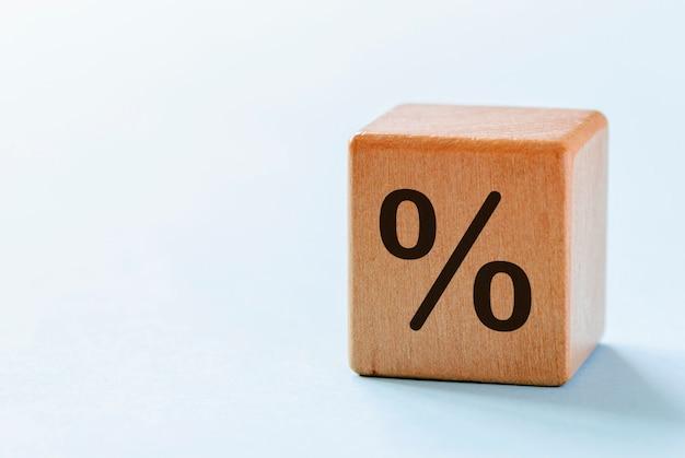 Un dado di legno con il simbolo delle percentuali
