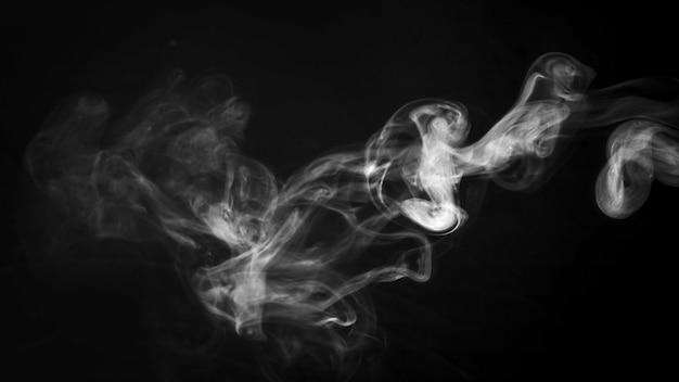 Un denso disegno di fumo che volteggia davanti a uno sfondo nero
