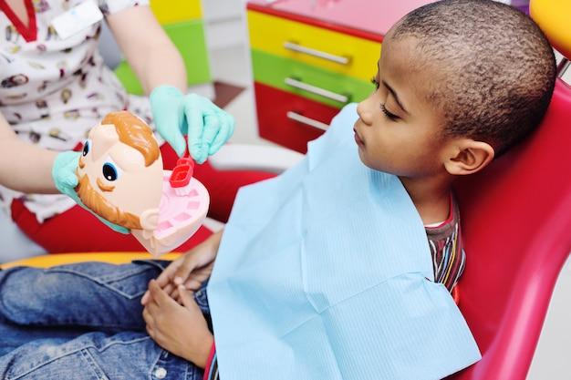 Un dentista pediatrico insegna a un bambino afroamericano che siede in una poltrona per lavarsi i denti correttamente.