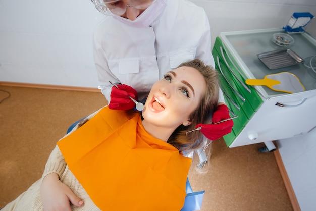 Un dentista professionista esegue il trattamento e l'esame della cavità orale del paziente in primo piano. odontoiatria