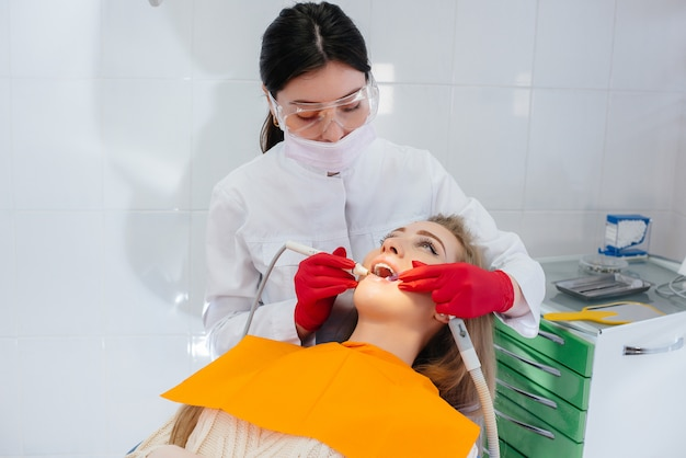 Un dentista professionista esegue il trattamento e l'esame della cavità orale del paziente in primo piano. odontoiatria.