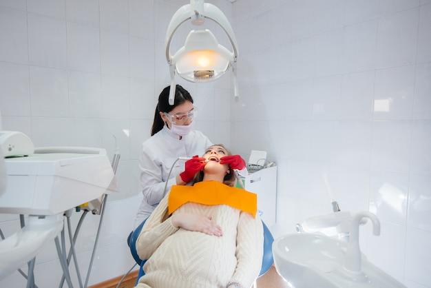 Un dentista professionista tratta ed esamina la cavità orale di una donna incinta in un moderno studio dentistico. odontoiatria