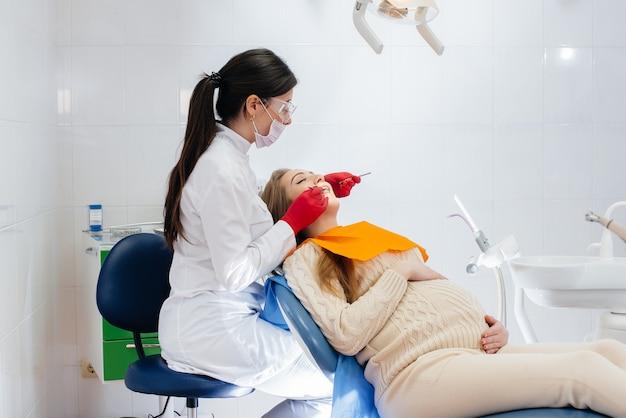 Un dentista professionista tratta ed esamina la cavità orale di una ragazza incinta in un moderno studio dentistico. odontoiatria