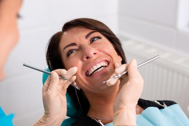 Un dentista termina con successo un restauro dentale, un medico consiglia un paziente felice