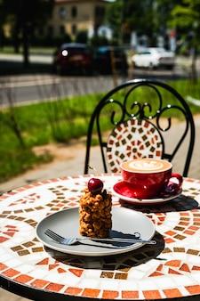 Un dessert muraveynik e una tazza rossa appena fatta di cappuccino su un tavolo di pietra a mosaico di una terrazza del caffè in una giornata di sole