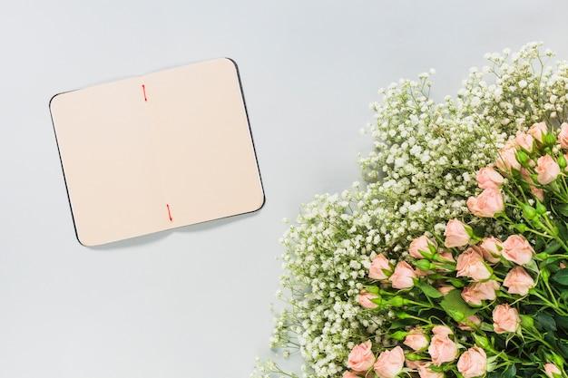 Un diario in bianco aperto con bouquet di fiori su sfondo bianco