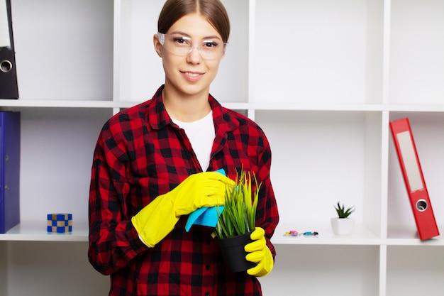 Un dipendente di un'impresa di pulizie pulisce la polvere sulle piante