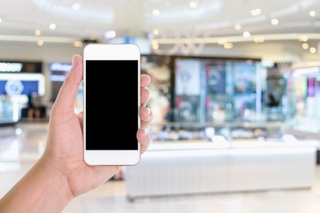 Un dispositivo dello smart phone della tenuta della mano dell'uomo con lo spazio in bianco dello schermo della copia in un grande magazzino