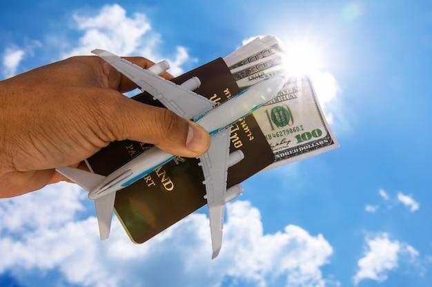 Un dollaro e un passaporto e l'aereo di un uomo su uno sfondo di cielo.