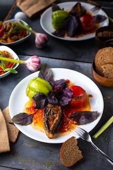 Un dolma vista frontale con carne macinata all'interno di olio di verdure all'interno del piatto bianco insieme a pagnotte di pane fiori sul piatto di manzo tabella grigia