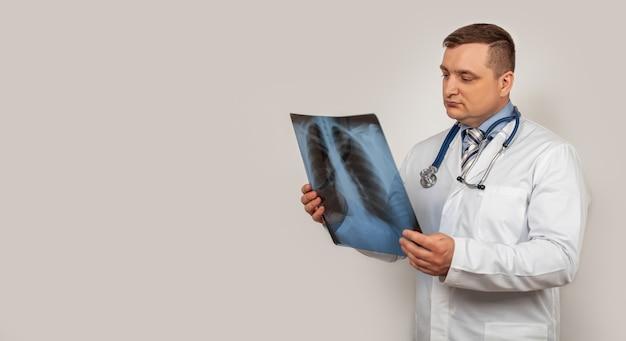 Un dottore maschio guarda e studia una radiografia del torace. un'istantanea dei polmoni di una persona con segni di polmonite.