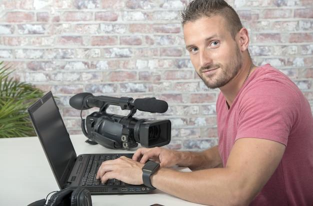 Un editor video con laptop e videocamera professionale
