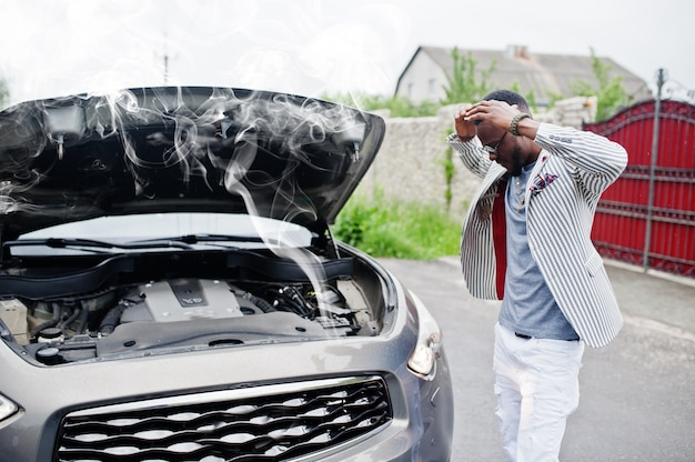 Un elegante e ricco uomo afroamericano in piedi davanti a un'auto suv rotta ha bisogno di assistenza guardando sotto il cofano aperto con il fumo.