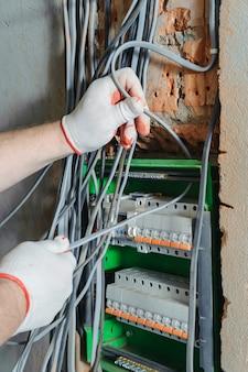 Un elettricista sta installando i cavi elettrici in una scatola dei fusibili di commutazione.