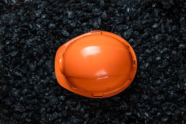 Un elmetto arancione di un minatore giace su un mucchio di carbone, miniere di carbone a cielo aperto, copia spazio.