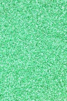 Un'enorme quantità di paillettes decorative verdi. immagine con luci bokeh splendente da piccoli elementi