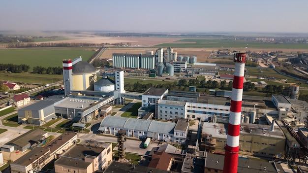 Un'enorme raffineria di petrolio con strutture metalliche, tubi e distillazione del complesso con luci accese al crepuscolo. vista aerea