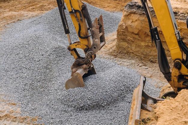 Un escavatore giallo che sposta ghiaia nelle fondamenta della casa.