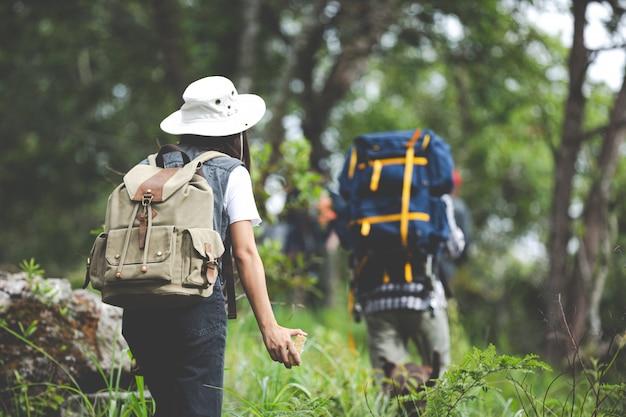 Un escursionista felice cammina attraverso la giungla con uno zaino.