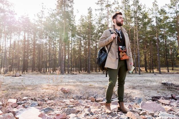 Un escursionista maschio con fotocamera e zaino in piedi nella foresta