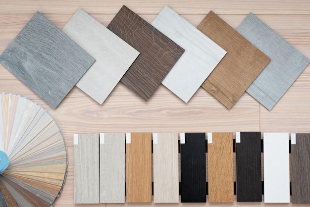 Un esempio di un catalogo di lussuose piastrelle per pavimenti in vinile e una tavolozza di design con trame con un nuovo design d'interni per una casa o un pavimento su un tavolo di legno chiaro.