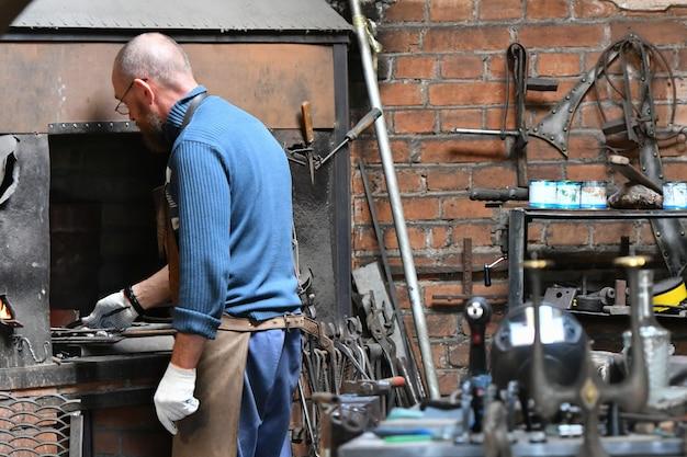 Un fabbro esperto lavora a fuoco aperto. un fabbro spegne una fiamma in una fucina con un fuoco d'artificio a scintilla, forgia ferro caldo in un'officina