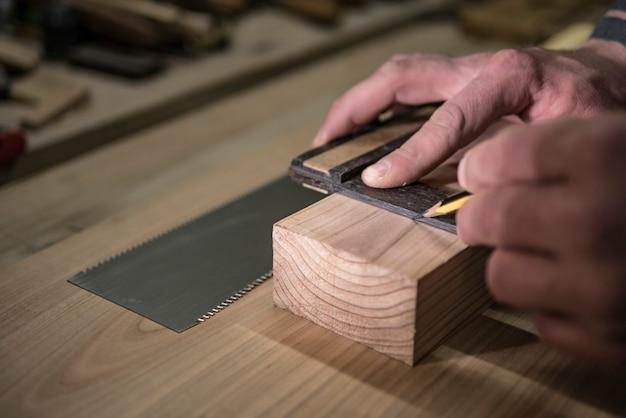 Un falegname con una matita e un quadrato segna il pezzo
