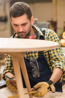 Un falegname maschio che misura la tavola di legno con il righello