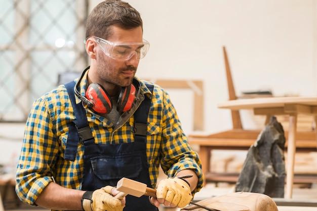 Un falegname maschio che scolpisce la forma di legno con lo scalpello nell'officina