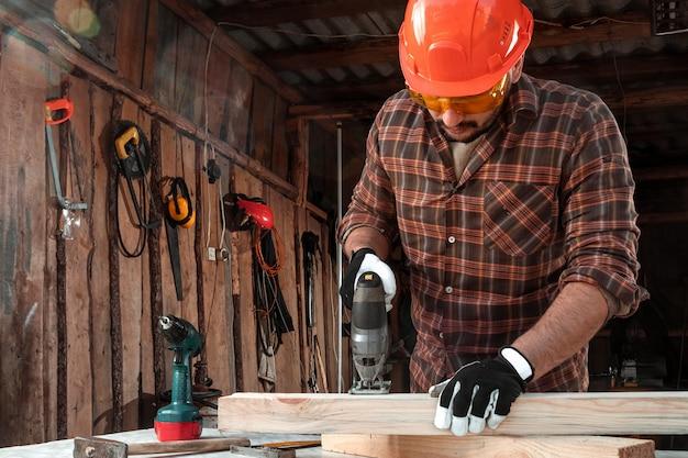 Un falegname uomo taglia una trave di legno usando un puzzle elettrico, mani maschili con un primo piano elettrico del puzzle.