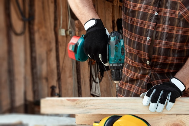 Un falegname uomo torce una vite in un albero con un cacciavite elettrico, mani maschili con un cacciavite close-up.