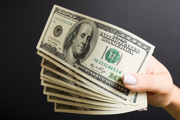 Un fan di cento banconote in dollari in mano femminile su sfondo colorato. concetto di investimento